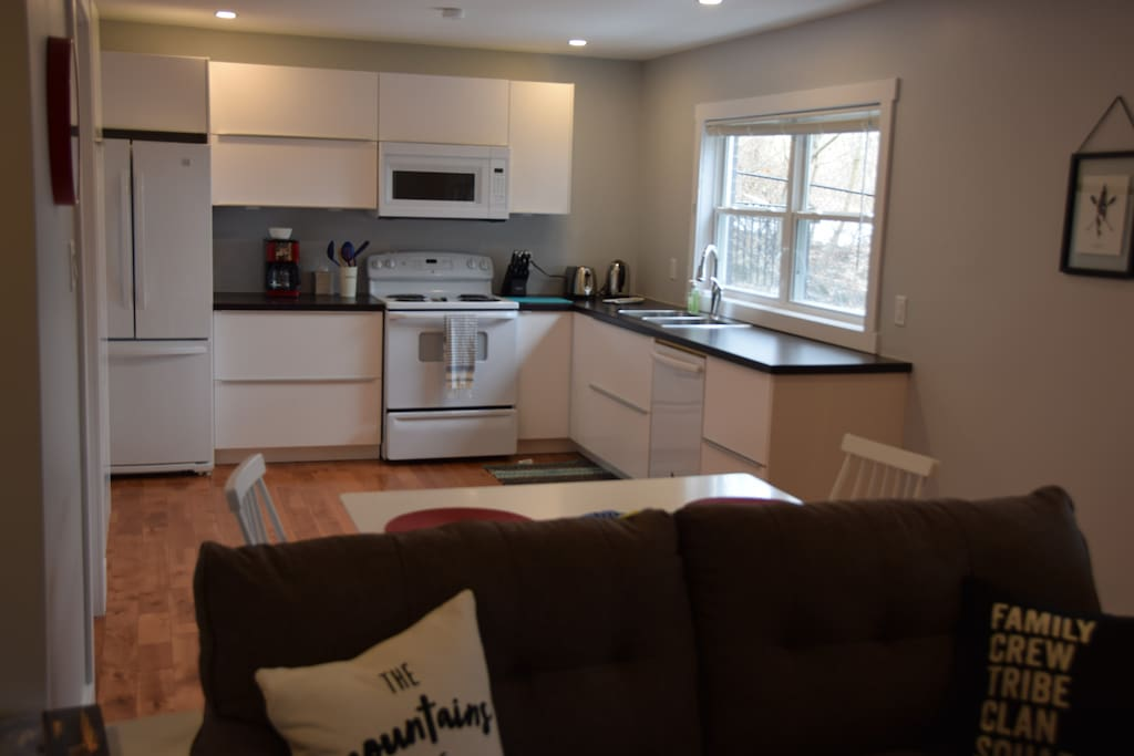 Bright kitchen with coffee maker, toaster, kettle, dishwasher and all your necessities