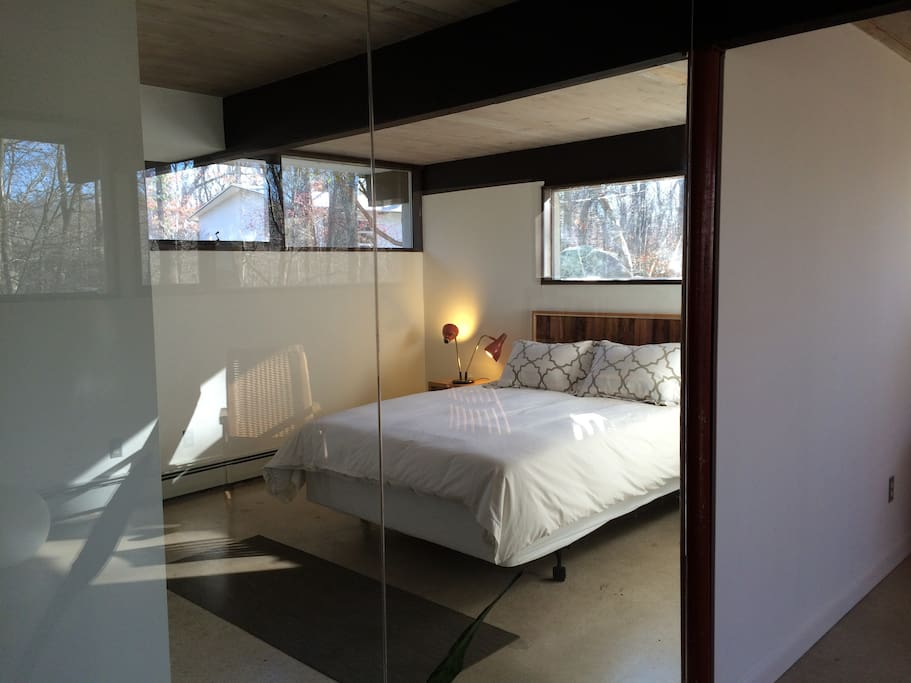 Bedroom has glass wall to create spaciousness. It has a curtain for privacy.