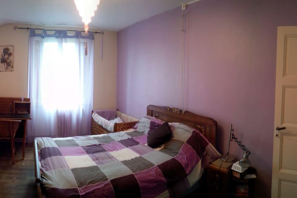 Première grande chambre avec un lit double, avec un bureau et une penderie. De plus un lit pour bébé est à disposition