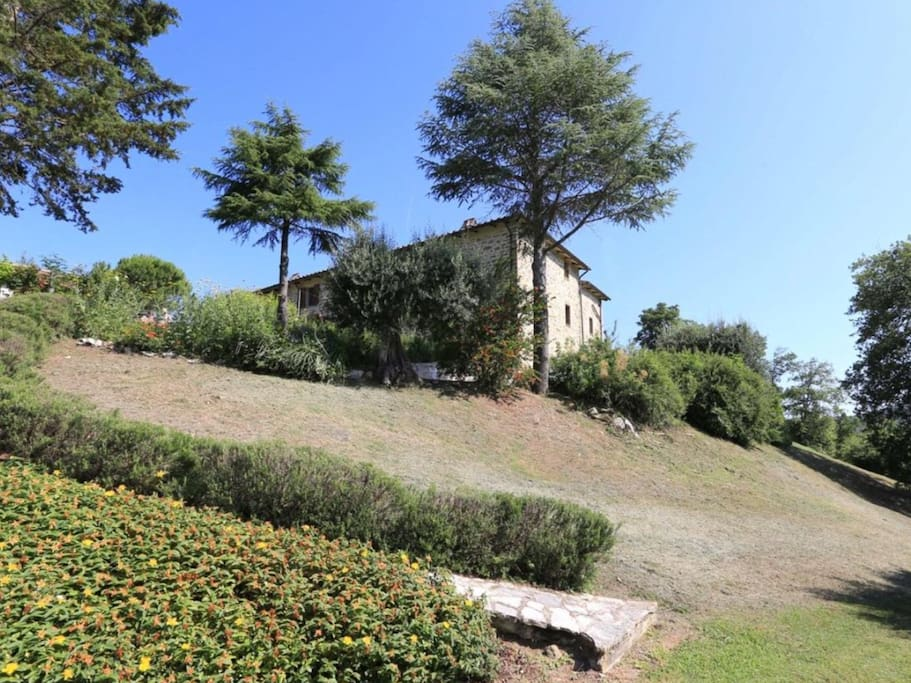 The farmhouse. Crinale apartment is shown here on the second floor with far reaching views over the olive grove and Umbrian hills