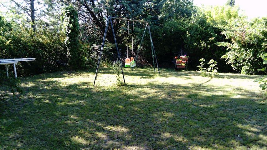 jardin avec balançoire et réserve de bois pour barbecue !