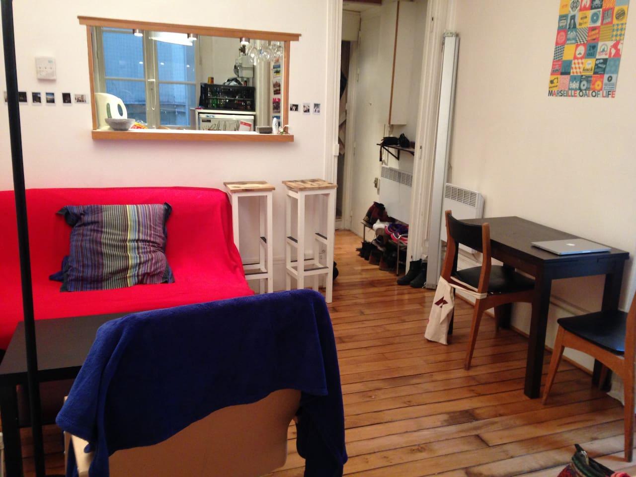Salon avec lit clic-clac 2 places et cuisine ouverte.
