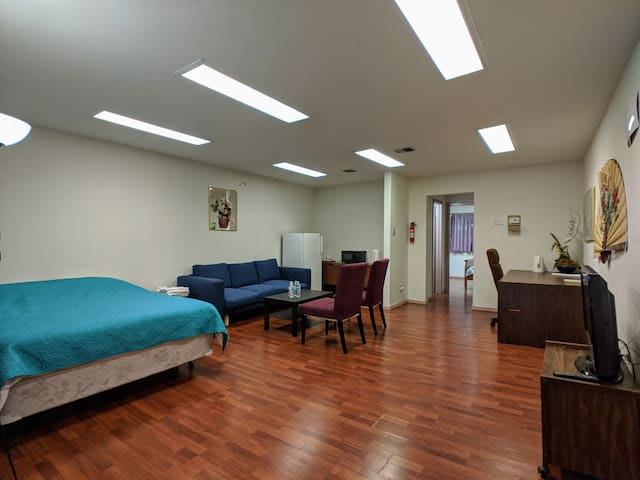 Living room with sofa and chairs, desk, queen size bed, medium size refrigerator, microwave and TV.