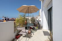 terrace with a table, 4 chairs and a  Beach umbrella. a perfect space to have your breakfast or a drink in the evening.