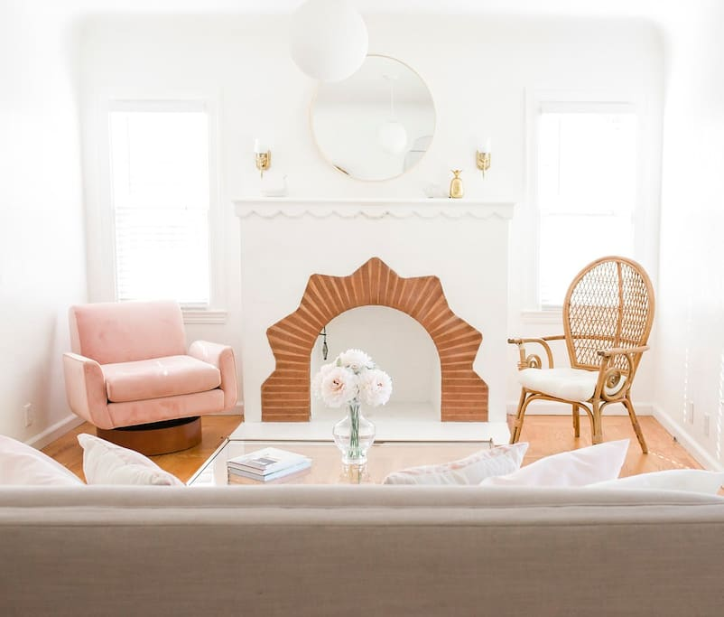 Stylish pink modern chair & rattan chair are statement home decor pieces in this cheery home.