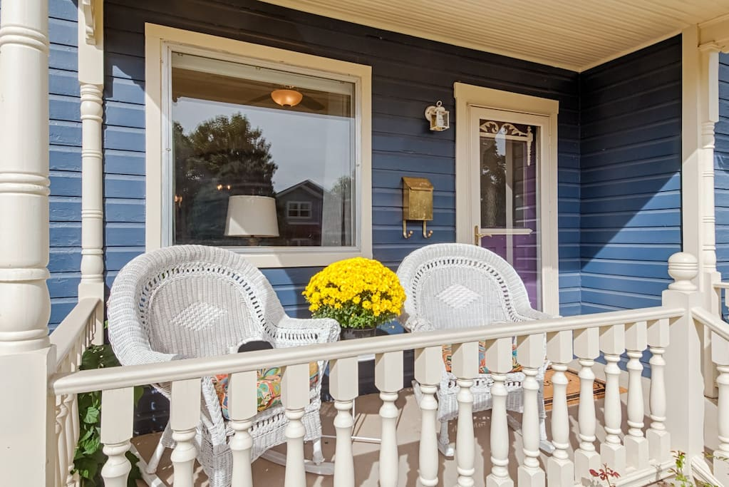 Covered front porch with wicker rockers perfect for relaxing and watching the world go by.