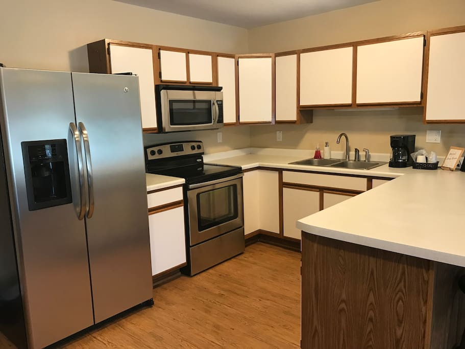 Full kitchen - Fridge, microwave, oven/stove, and coffee maker.