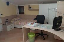 Stanza con letto, scrivania e armadio