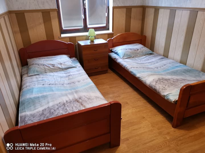 Single bed in twin room with shared bathroom.