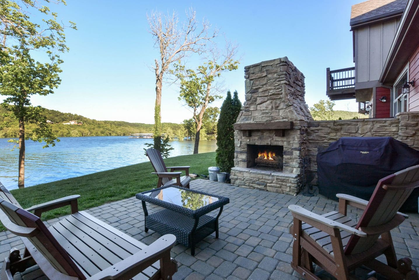Outdoor luxury seating with stone fireplace and top of the line Weber gas grill.