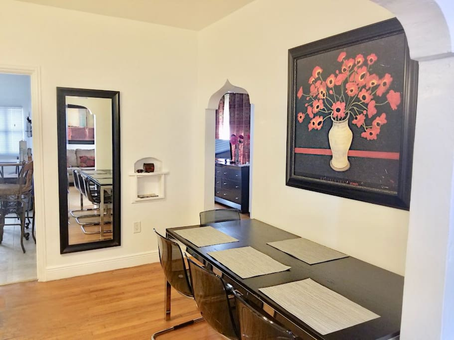 Large dining room table in mid area and additional table seating off in kitchen