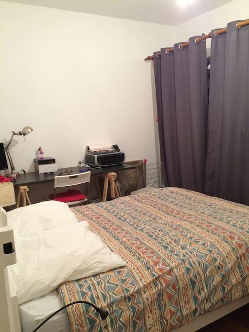 Une chambre avec lit 2 places et un grand bureau ainsi qu'un espace réservé dans le dressing.