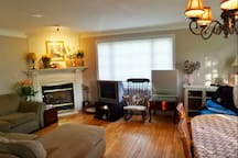 Downstairs common area - Cable TV, fireplace, couches, hardwood floor