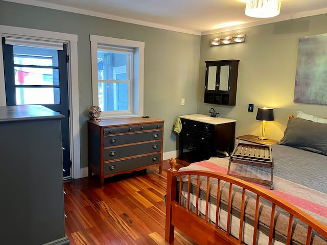 Master bedroom with Queen, walk in closet with hangers and extra linens, European-style sink vanity, two dressers, bedside tables with lamps, a small fan, and a balcony accessible only from the bedroom with seating. Room's own heating/cooling unit.