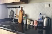 we provide Mineral waters (also in refrigerator), electric kettle (for hot water), tea bag, instant noodle, & oat for breakfast. Theres tableware in the cabinet too.