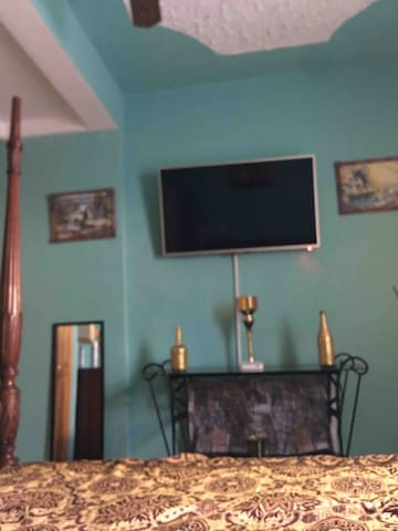 Television in bedroom with king size bed