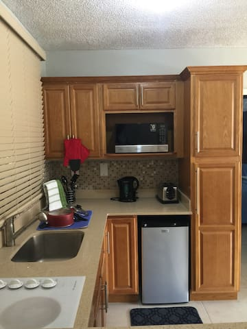 Kitchen with electric stove, mini refrigerator, microwave, toaster and kettle. Also includes pots and pans, dining set and utensils.