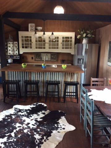 Lovely farmhouse kitchen with full amenities, large farm sink, dining table and bar seating,  just to mention a few.