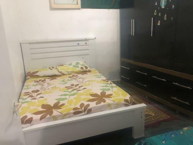 Quarto com banheiro cama de casal guarda roupa e cabides  e uma cama de solteiro com dois colchões