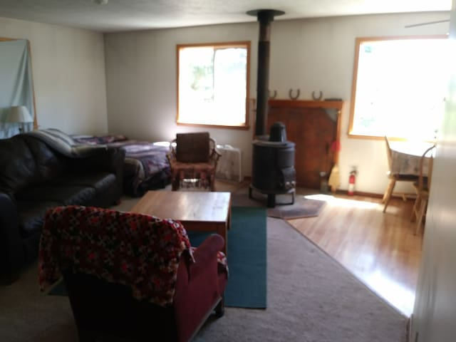 Living room has leather couch, 2 chairs and futon in the corner.
