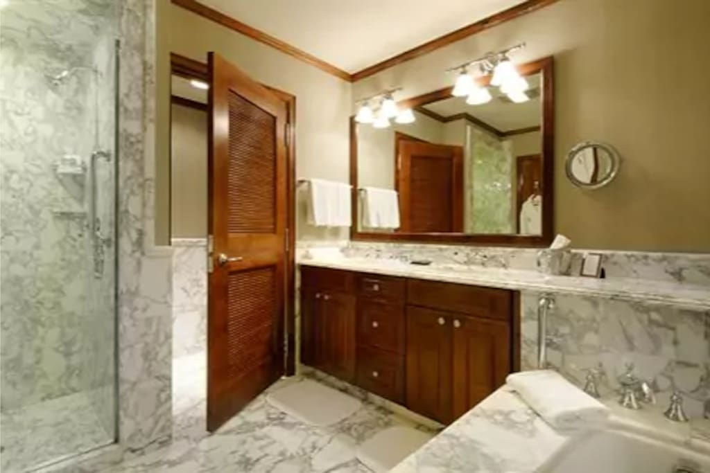 Large bathrooms with double sink, tub and show