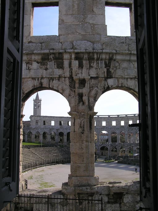 Arena Pula and in the background the bell tower of the church of St. Anthony of Padua in Pula with 45 m high tower. from the 1930s.