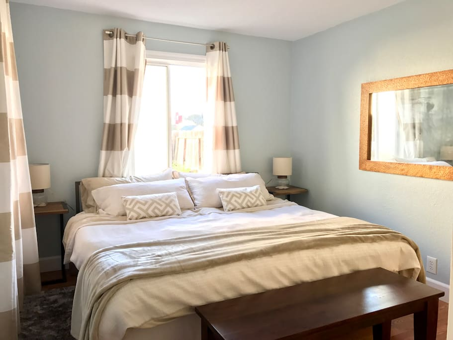 The bedroom, with medium-firm latex and memory foam king bed, down pillows, down comforter, cotton bed linens, and blackout curtains. The king bed can be split into two singles.
