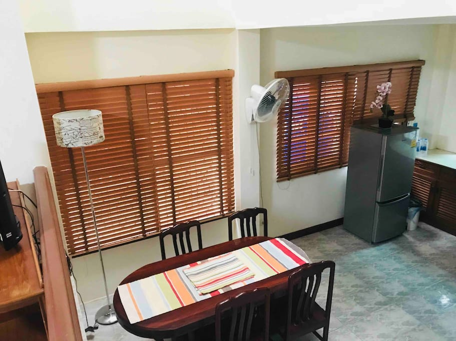 Dining table in a big space of kitchen area plus a refrigerator