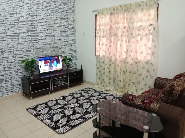 ruang tamu, tv (siaran MyTV), sofa dan ruang saterika.