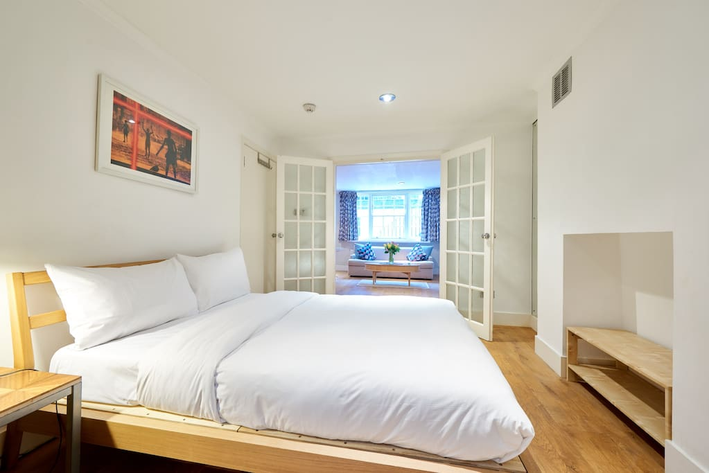 Double doors open onto the spacious bedroom, with a comfy bed fitted in fresh luxury linen