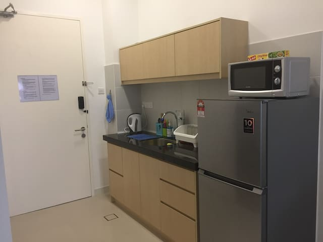 Functional kitchen with microwave, water boiler, induction cooker, toaster, fridge, utensils and saucepan.