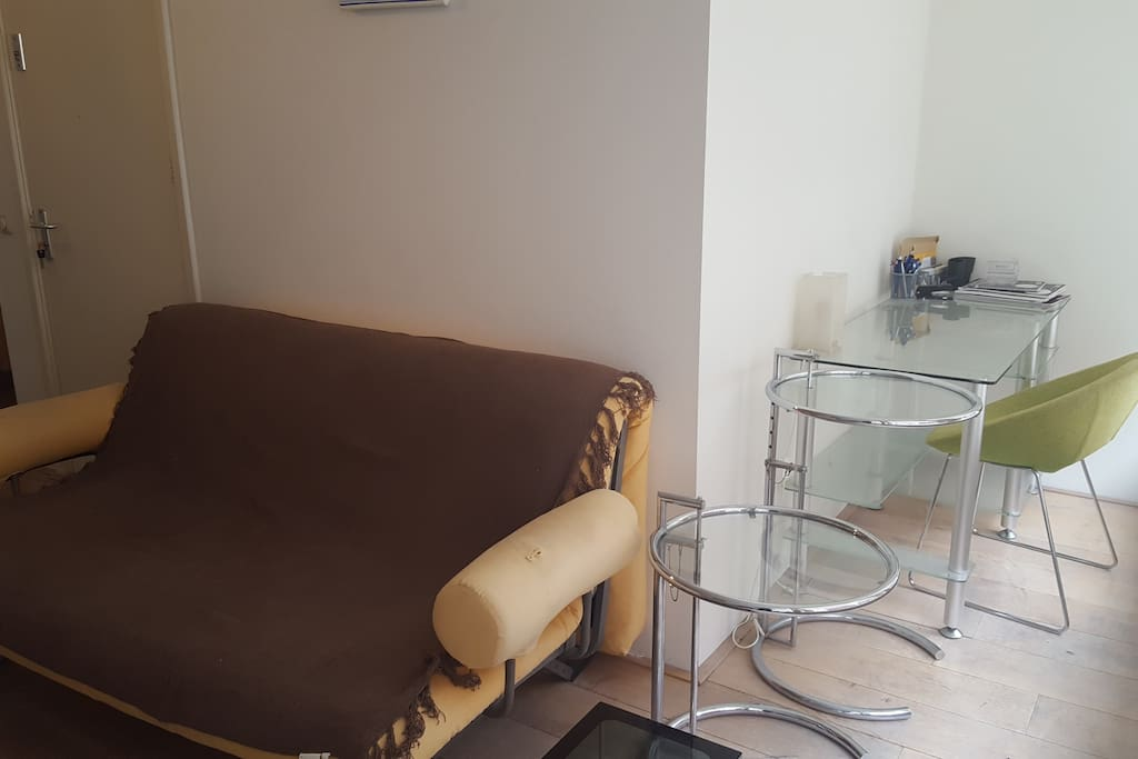Living area and a small desk on first floor. Sofa opens into double bed