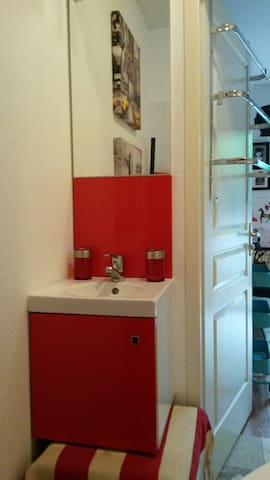 SDB privative: meuble lavabo avec petit rangement. Mise à disposition d'une desserte sur roulettes à 3 compartiments pour vos affaires de toilettes.