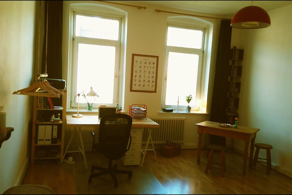 sunny and spacious room with a desk, a place to store your luggage in and a little table.