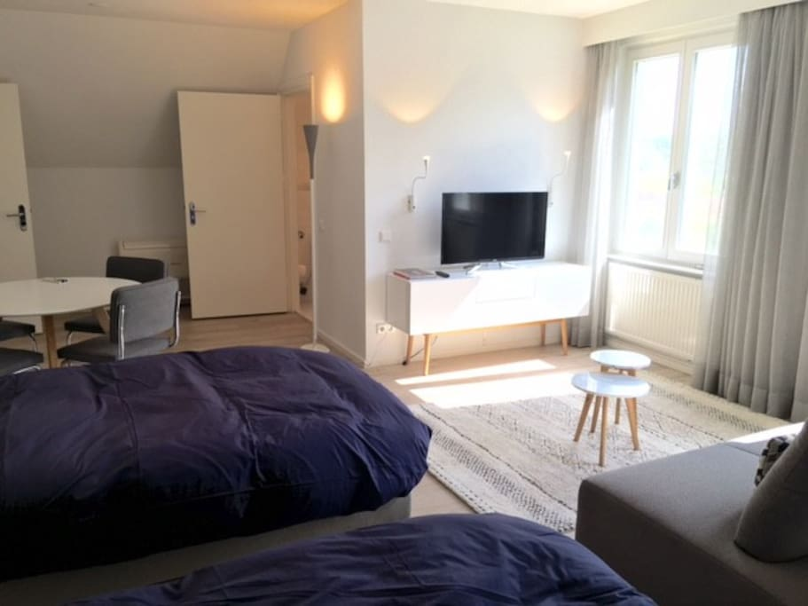 Twin room with Ensuite bathroom, lounge area and dining table for 4.