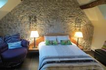 Mur en pierre. Ambiance chaleureuse. Cosy main bedroom with large built-in wardrobe. Tea/coffee making facilities.