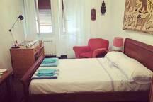 Camera da letto matrimoniale spaziosa con scrivania, poltrona, ventilatore e armadio. (Ombrellone da spiaggia)