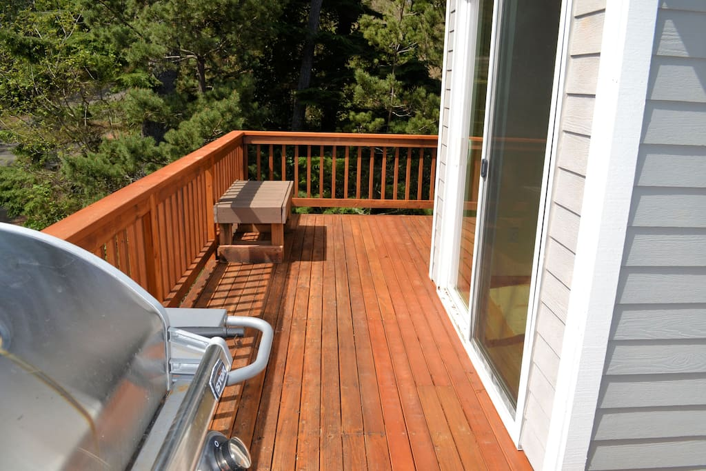 Upper deck off living area with a bench seat and gas BBQ