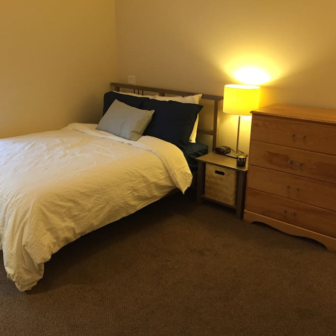 This is your bedroom. This is a double bed, and the dresser is empty for your use.