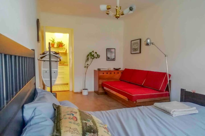 Double bed and red couch in beadroom