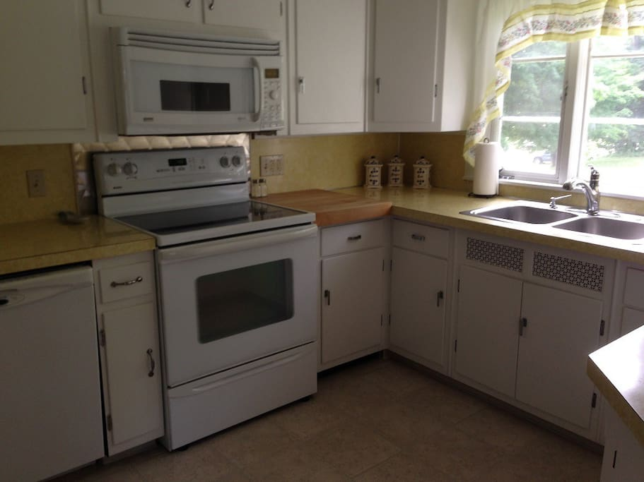 Kitchen with electric stove, microwave, dishwasher, garbage disposal