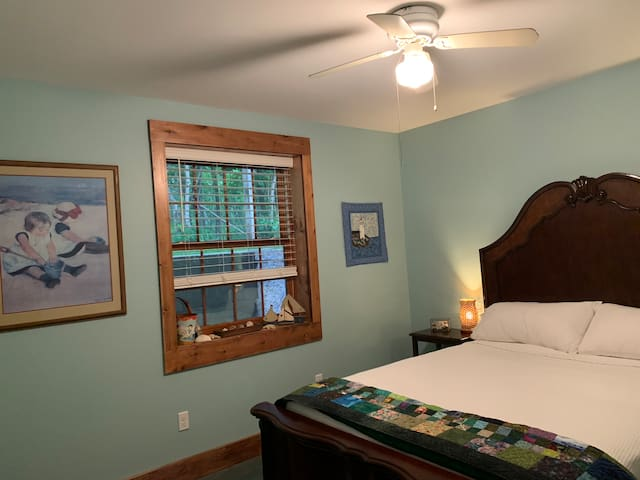 Bedroom 2 cool, relaxing, beach vibe queen bed and suitcase bench.
