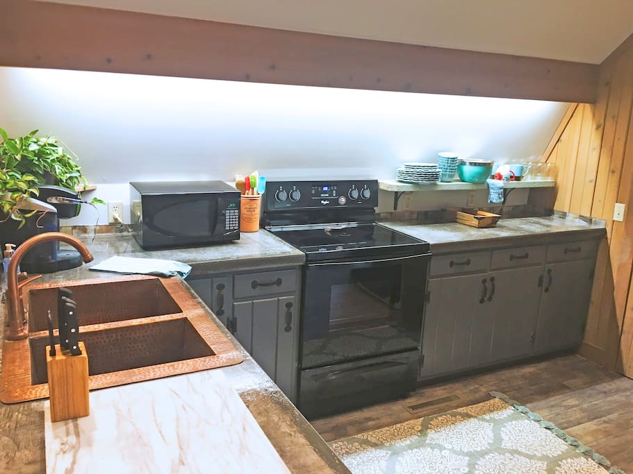 Modern kitchen with dishes, utensils, cookware, and other necessary items for cooking. You may find yourself wanting to eat in instead of eating out.