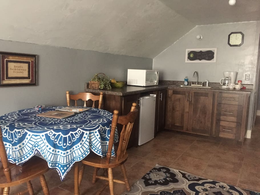 Full kitchen with a cook top stove, microwave and cookware.