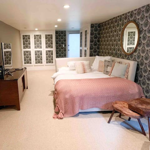 Queen bed/daybed in garden level with Farrow and Ball wallpaper.  Adjacent to twin bedroom with tv