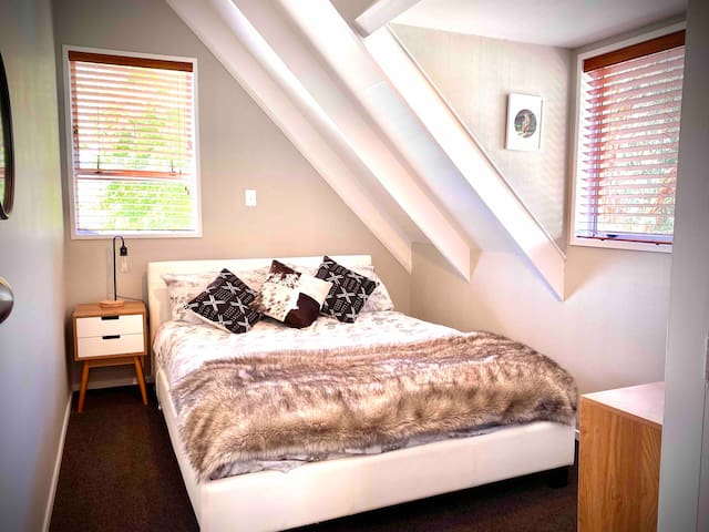 The 'Wilderness Bedroom' with queen bed, drawers and wardrobe upstairs.