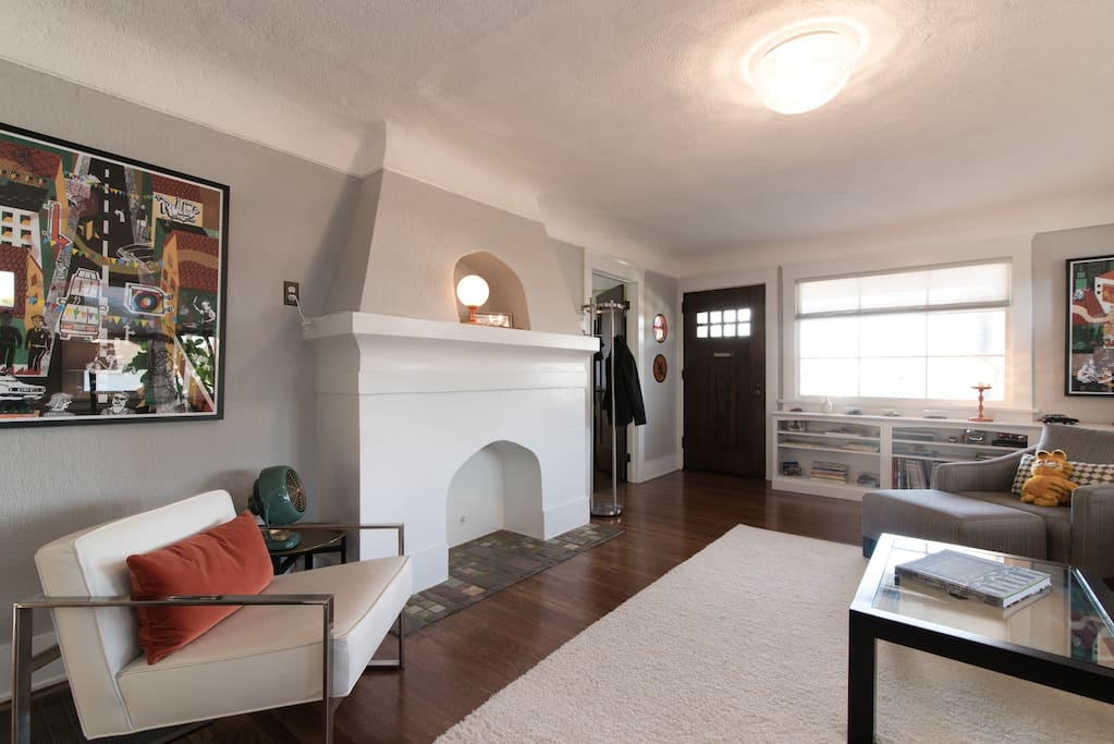 Enter directly into a bright and spacious living room with original decorative fireplace.