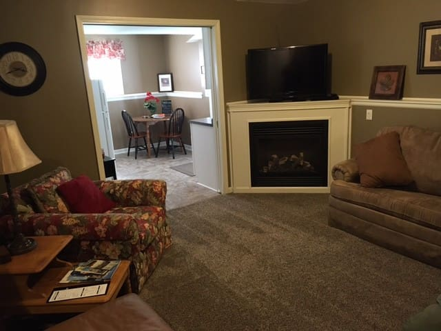 Living room showing gas fireplace and looking into kitchen and apartment entrance area.
