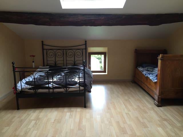 Grande chambre sous-pentes avec lit supplémentaire.