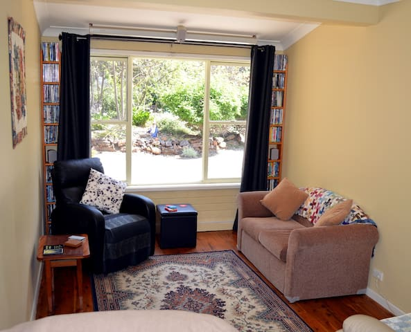 Sitting area with massage chair, games, reclining chairs, table and stools plus projector with a wide selection of dvds to enjoy